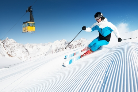Skier in mountains, prepared piste and sunny day photo