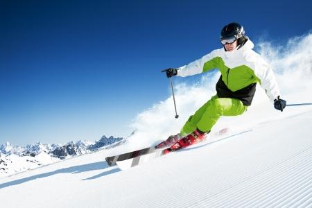 ski�r: Skiër in bergen, geprepareerde piste en zonnige dag Stockfoto