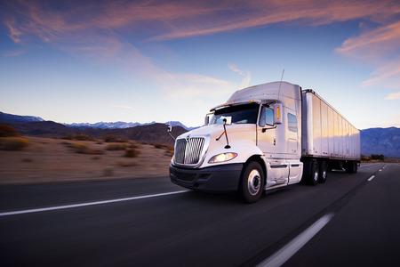 transporte de mercancia: Camiones y carretera al atardecer - fondo de transporte