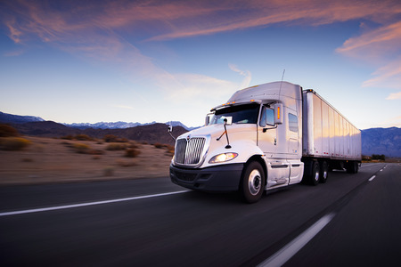 freight: Truck and highway at sunset - transportation background Stock Photo
