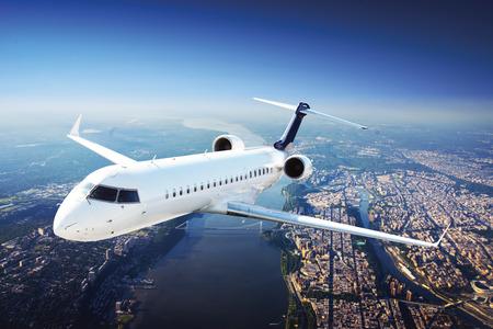 市内から飛んでいる空の私用ジェット機 写真素材