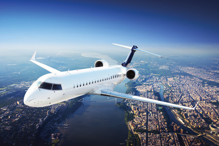 airplane: Private Jet Plane in the sky flying from city Stock Photo