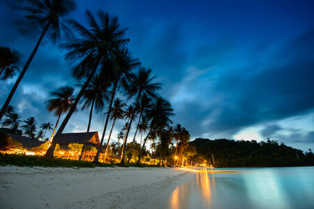 Bungalows, palms and beach at sunset in thailand paradise Imagens