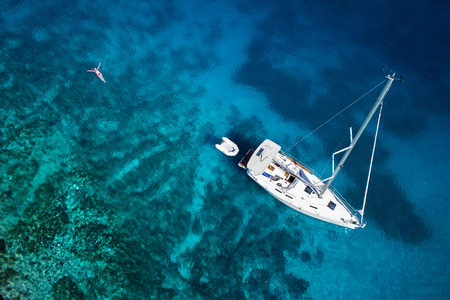 amazing view to yacht, swimming woman and clear water caribbean paradise Standard-Bild