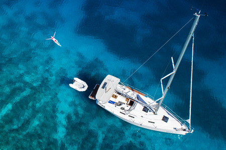 blue top: amazing view to yacht, swimming woman and clear water - caribbean paradise Stock Photo
