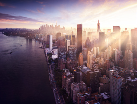 New York City - beautiful colorful sunset over manhattan fit sunbeams between buildings photo