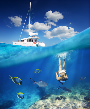Girl diving in ocean with fishes next to catamaran at sunny day