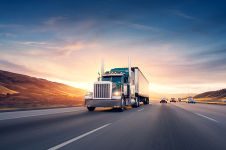 American style truck on freeway pulling load. Stock Photo