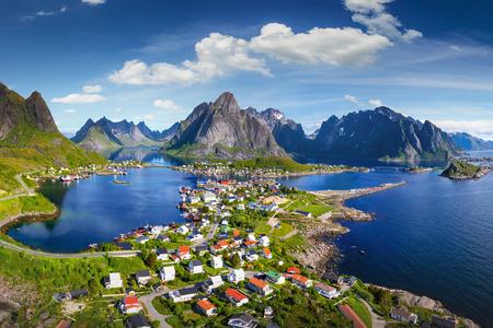 Reine, Lofoty, Norwegia. Wioska Reine pod słonecznym, błękitnym niebem, z typowymi domami rorbu. Widok z góry