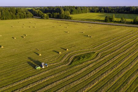 Tractor working in the field with hay to get it dried under the heat of the summer sun. Agriculture field haystack. Landscape with drone
