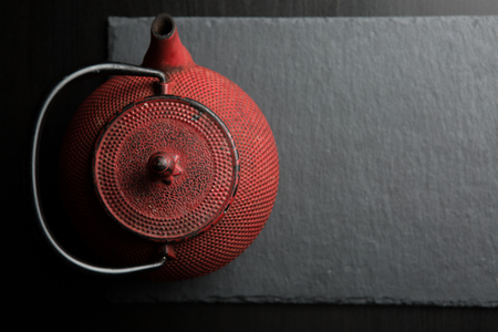 Traditional red iron teapot with dark color background