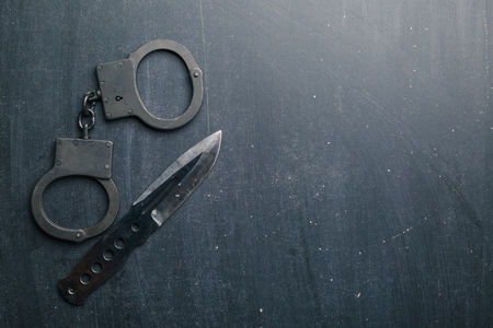 Tactical gear set of knife and handcuff on dark background. Police or military equipment concept.