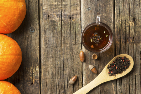 glass cup with teaand acorns and wooden spoonful of berry herbal tea on old wooden table Stock Photo