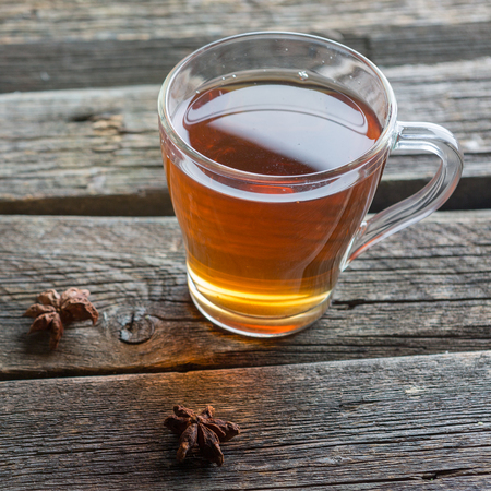 A glass cup of black tea on a wooden table. Stock Photo