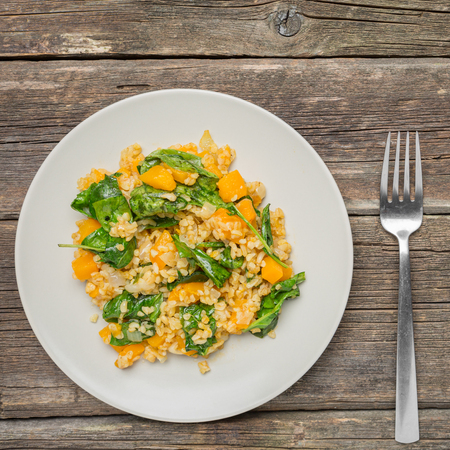 Bulgur with Vegetables:pumpkin, onion and spinach on wooden background - healthy homemade organic vegan vegetarian diet food Stok Fotoğraf