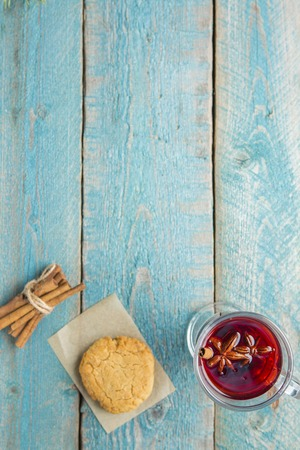 Christmas Mulled Wine with cookies and bunch of cinnamon Decorated with Fir Branches on wooden background
