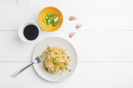 Noodles with bell pepper on plate and garlic cloves and green chopped onion in litle bowl on white wooden background