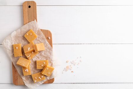 Homemade caramel fudge candies on white rustic background. Stock Photo