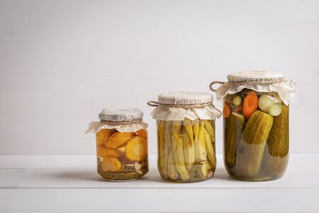 Marinated preserved squash, cucumbers and okra in jar on white backgrou 스톡 콘텐츠