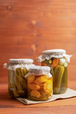 marinated assorted with cucumber and squash, dill, carrot, garlic and onion in a jar on wooden background with copyspace
