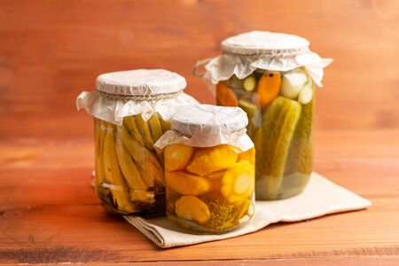 marinated assorted with cucumber and squash, dill, carrot, garlic and onion in a jar on wooden background