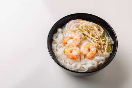 Traditional vietnamese noodle soup pho with shrimps in black bowl on white background