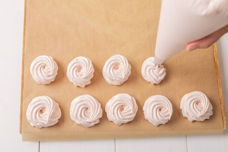 Close up hands of woman with confectionery bag cream to parchment paper at kitchen. Homemade sweets top view
