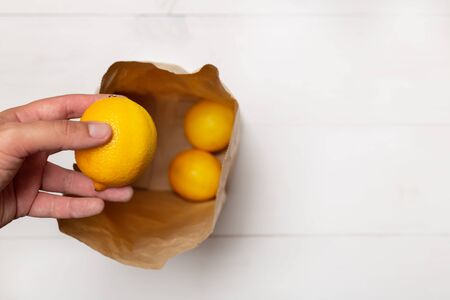 Male hand puts a lemon in a brown paper bag from top view looking down inside at bottom on white wooden background with copy space Foto de archivo
