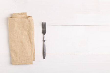 Fork and knife on beige napkin on white wooden table. Top view with copy space
