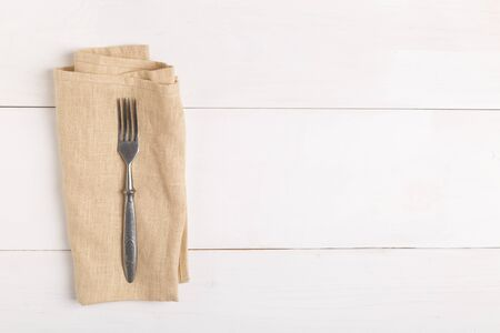 Fork and knife on beige napkin on white wooden table top view with copy space