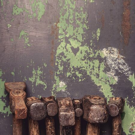 Set of old hammers and rusty nails. tools on old metal the surface. Top view with copy space tonned image