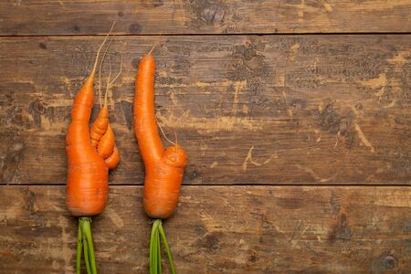 Ugly carrots on wooden background freshly picked from garden. Organic food concept. Top view with copy space.