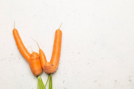 Funny ugly carrots on threadbare white surface top view with copy space.