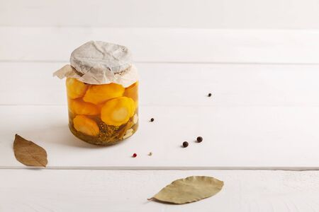 Glass jar with canned squash and spice on white wooden background