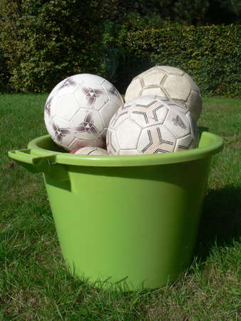 stocked: Worn out soccer balls in a green basket