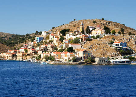 Colorful architecture of the buildings of the rocky shore of the island Symi, Greece.