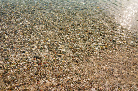 The coastal shingle of the seabed in clear water, background.
