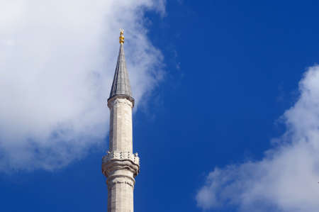 The minaret of the Fatih mosque on the blue sky background.