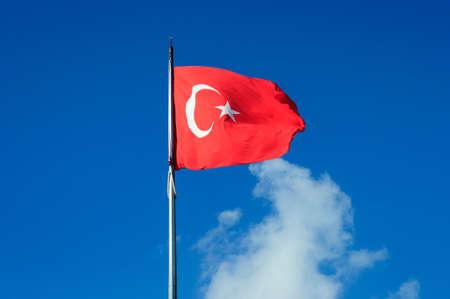 Turkish flag flying on flagpole against blue sky, Istanbul, Turkey. Banco de Imagens