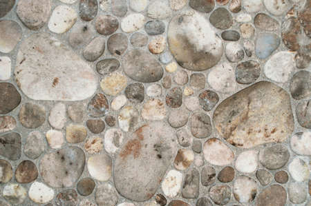 The surface of the wall of round pebble stone, background. Banco de Imagens