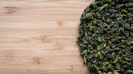 Top view dry green tea leaves on a wooden board. Imagens