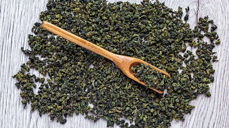 Dry green tea leaves in a wooden spoon.
