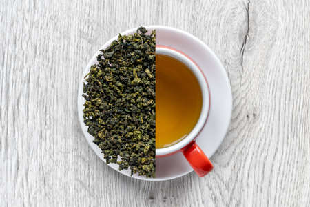 Tea in a cup and dry green tea leaves on a white plate.