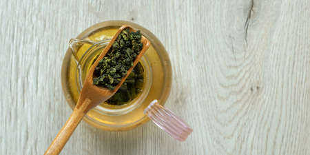 Top view dry tea leaves in a wooden spoon.