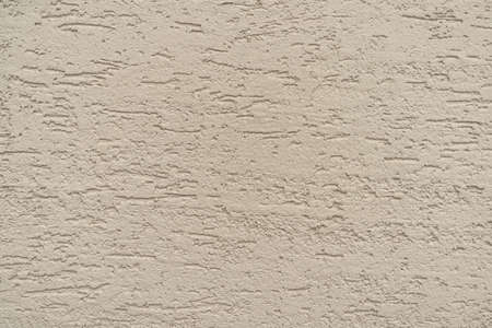 The texture of beige relief decorative plaster, background. Imagens