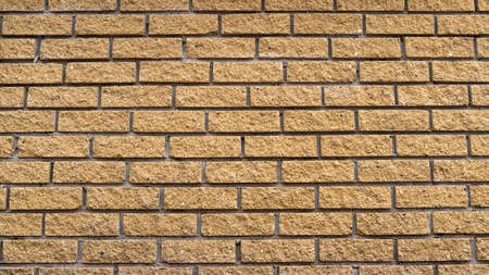The texture brown yellow decorative brick wall, background.