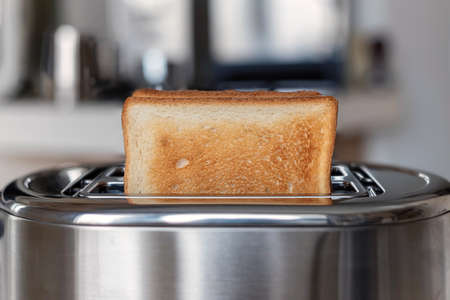 Fried white bread toast on the toaster, background