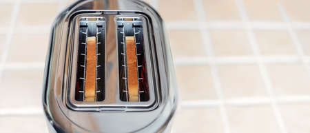 Toasts of bread are fried in a toaster oven, background.