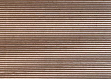 The texture of horizontally corrugated brown cardboard, background.