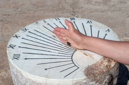 Hand on a vintage stone sundial, Carthage.